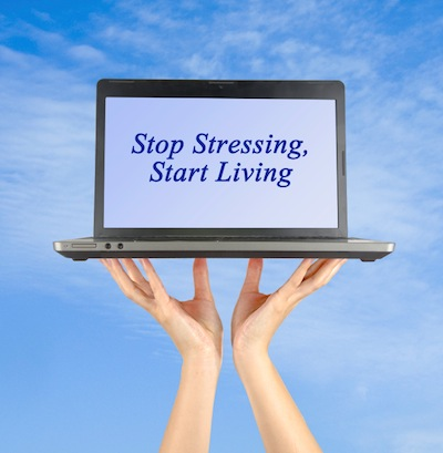 Image of hands holding up a laptop computer with the words 'stop stressing, start living' on the screen